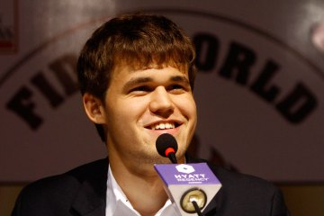 Norway's Magnus Carlsen smiles as he speaks with the media at a news conference after clinching the FIDE World Chess Championship in the southern Indian city of Chennai